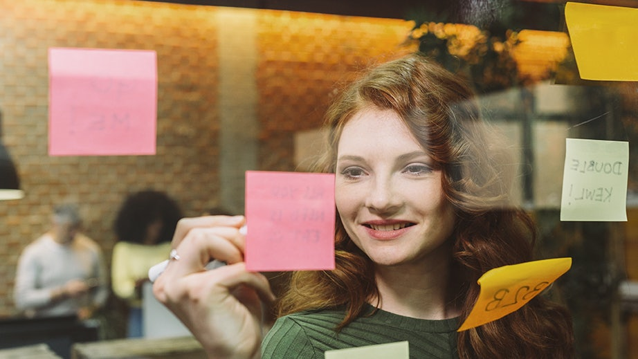Woman writing on Post it note